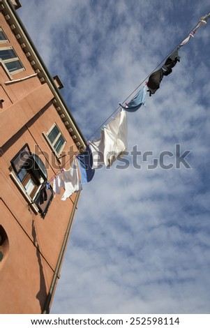 Clothes drying in the wind, hanging on a clothesline between buildings, Venice, Italy