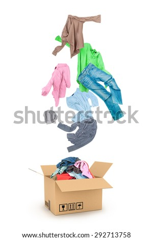 clothes falling into the cardboard box isolated on white  - stock photo