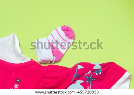 Clothes for baby girl on light green background. Copy space for text