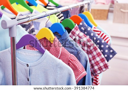 Clothes for children on hangers in a room