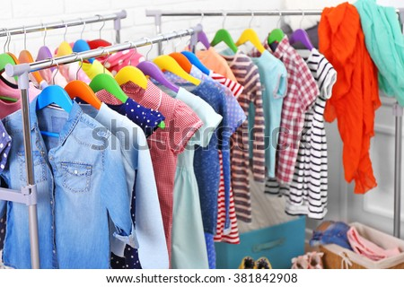 Clothes for kids on hangers - stock photo