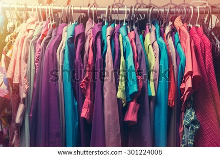 Clothes hang on a shelf in a clothes store - stock photo