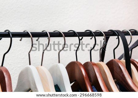 Clothes hang on a shelf in home - stock photo