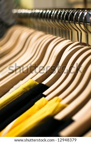 Clothes hangers with shirts in the fashion store. Clothes store concept - stock photo