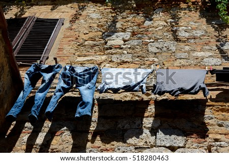 Clothes hanging at old brick and stone wall
