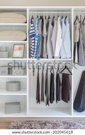 clothes hanging in white wardrobe with pillows and boxes - stock photo