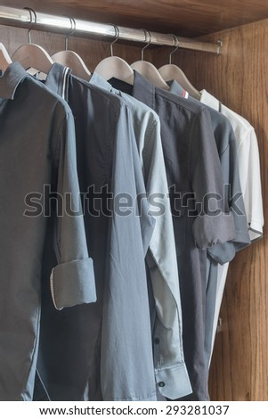 clothes hanging in wooden wardrobe at home