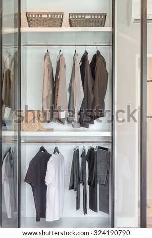 clothes hanging on rail  in white wardrobe at home