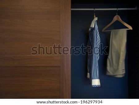 Clothes hung neatly in wardrobe wood - stock photo