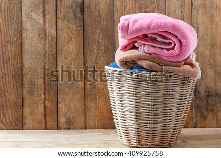 Clothes in a laundry basket on Wood floor - stock photo