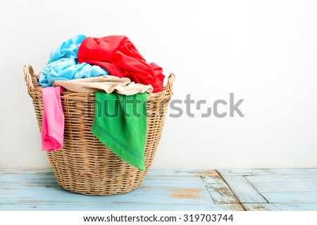 Clothes in a laundry wooden basket on wood table - stock photo
