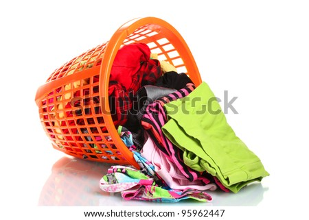 Clothes in orange plastic basket dropped isolated on white - stock photo
