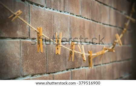 clothes line for hanging photos against a grungy brick wall
