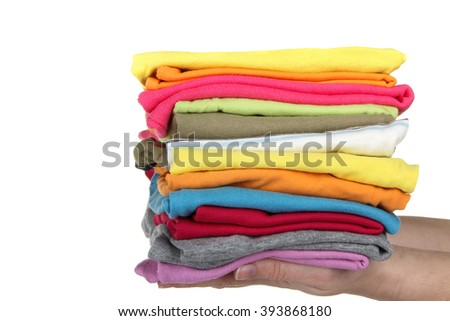 clothes neatly folded and lying on the hands of women isolated on white background - stock photo