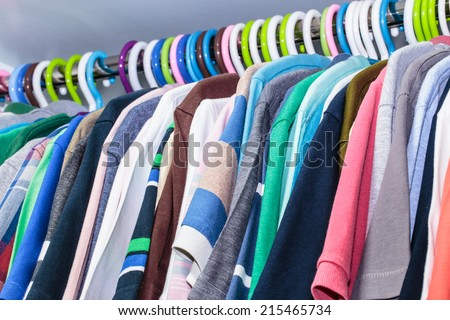 Clothes of different colors on plastic hanger - stock photo