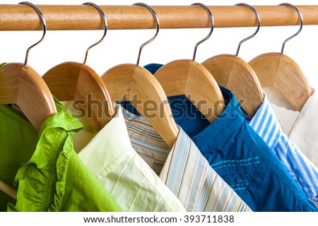 Clothes on wooden hangers isolated on white background. - stock photo
