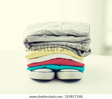 clothes, personal staff and objects concept - close up of folded shirts, pants and shoes on table at home - stock photo