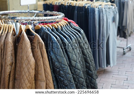 clothes rack with a quilted winter jackets and jeans for sale - stock photo