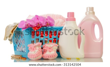 Clothes with detergent and baby's booties over plastic basket - stock photo