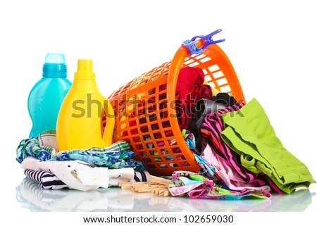 Clothes with detergent and in green plastic basket dropped isolated on white
