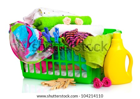 Clothes with detergent and in green plastic basket isolated on white - stock photo