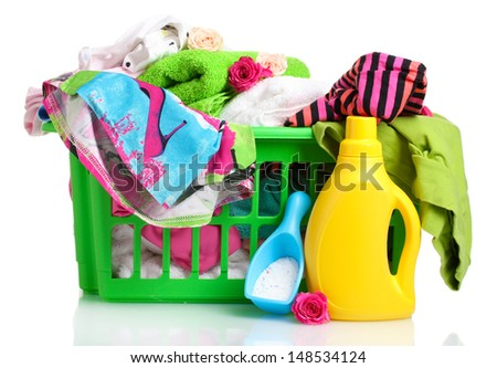 Clothes with detergent and washing powder in green plastic basket isolated on white - stock photo