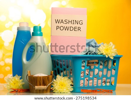 Clothes with detergent and washing powder in plastic basket on yellow background - stock photo