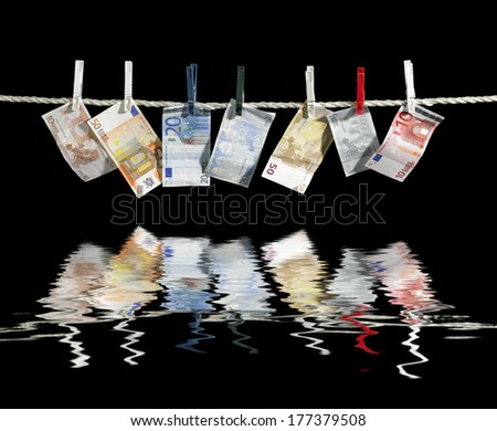 clothesline with some euro banknotes fixed with clothes pins on reflective water surface in black back - stock photo