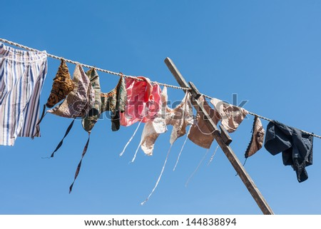 Clothesline with traditional Dutch clothes drying in the wind - stock photo