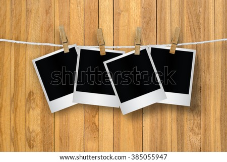 Clothespin hanging with blank photo papers on wooden background, with clipping path.