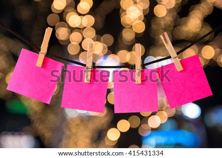 clothespin hanging with blank pink paper on abstract bokeh  background - stock photo