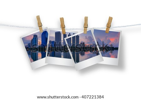 Clothespin hanging with photo cityscape skyscrapers of Bangkok, Isolated on white with clipping path. - stock photo