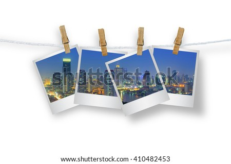 Clothespin hanging with photo cityscape skyscrapers of Bangkok, Isolated on white with clipping path.