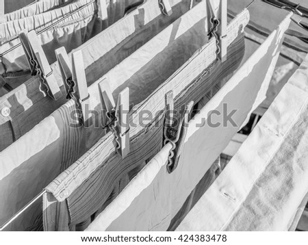 Clothespin or clothes peg spring loaded clamp in black and white - stock photo