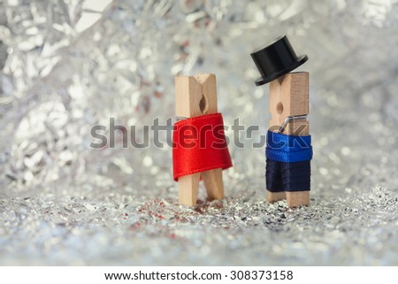 Clothespins: abstract romantic couple. Gentleman in black hat, woman in red dress. Soft focus, macro view. toned photo. shallow dof - stock photo