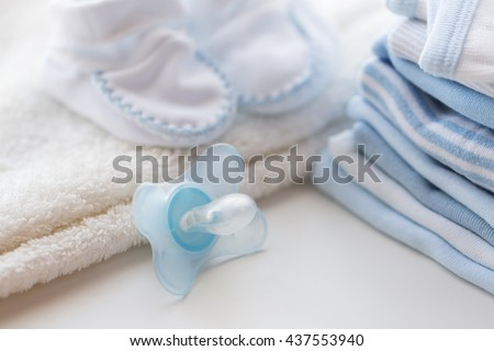 clothing, babyhood, motherhood and object concept - close up of baby soother, bootees and pile of clothes for newborn boy - stock photo