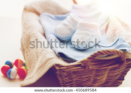 clothing, babyhood, motherhood and object concept - close up of white baby bootees with pile of clothes, towel and rattle for newborn boy in basket - stock photo