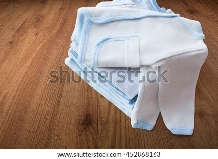 clothing, babyhood, motherhood and object concept - close up of white baby cardigan with pile of folded clothes for newborn boy on wooden floor background