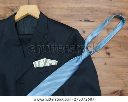 clothing concept. jacket and hanger. tie dollars on  wooden table