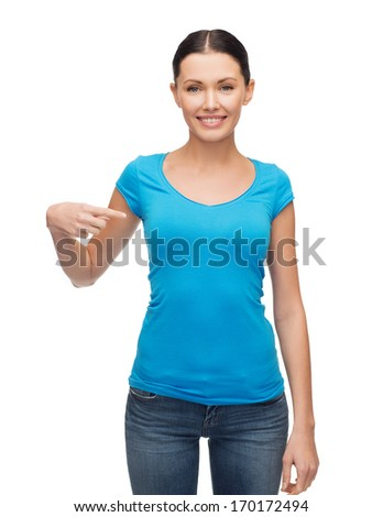 clothing design and gesture concept - smiling girl in blank blue t-shirt pointing her finger at herself - stock photo