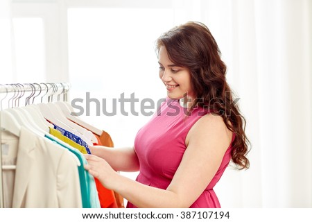 clothing, fashion, style and people concept - happy plus size woman choosing clothes at home wardrobe - stock photo