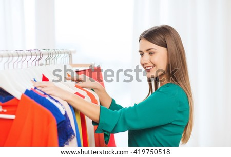 clothing, fashion, style and people concept - happy woman choosing clothes at home wardrobe - stock photo