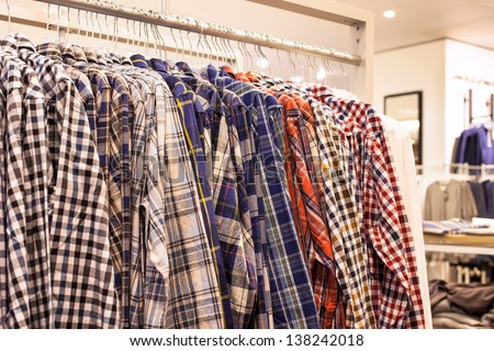 Clothing in Fashion Store - Checkered Mens Shirts on the Store Rack - stock photo