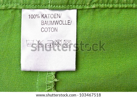 Clothing label washing instruction tag on green t-shirt