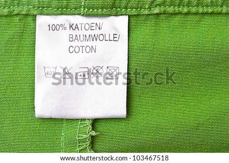 Clothing label washing instruction tag on green t-shirt - stock photo