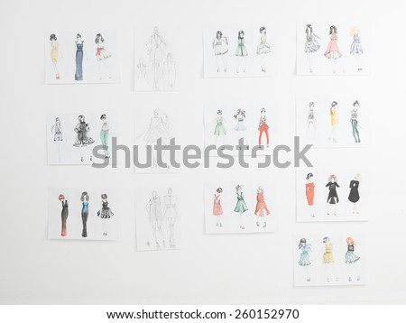 clothing sketches on wall in fashion designers studio - stock photo