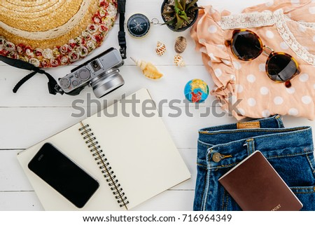 Clothing traveler's Passport, wallet, glasses, smart phone,notebook on a wooden floor in the luggage ready to travel.Travel concept