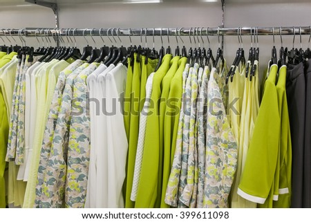 cloths hanging in wardrobe in the shop - stock photo