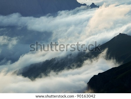 Cloud amongst mountains. White and dark lines