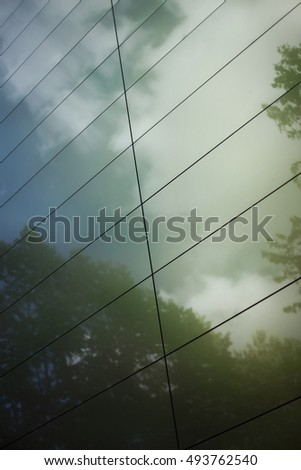 Cloud and trees reflecting on a modern facade